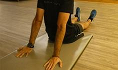 Homem a fazer alongamento de ombro - flexão, depressão e retração | Holmes Place