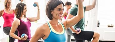 Grupo numa aula a levantar pesos | Fitness | Holmes Place