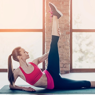 Woman stretching yoga mat gym | Holmes Place