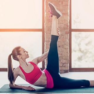 Woman stretching yoga mat gym | Holmes Place