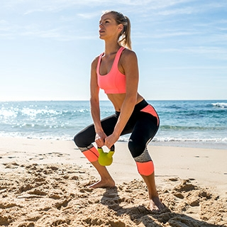 Holmes Place | woman weight lifting beach workout sunny sea