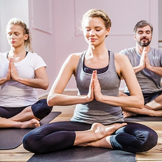 Indoor yoga class woman smiling namaste | Holmes Place