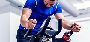 Homem a andar de bicicleta num treino LISS | Holmes Place